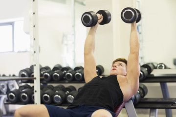 Muscular attractive man lying on bench training with dumbbells