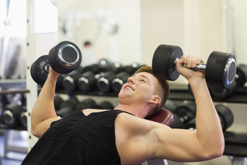 Muscular smiling man lying on bench training with dumbbells