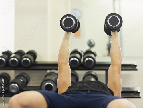 Muscular man lying on bench holding dumbbells