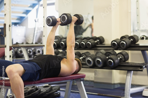Man lying on bench holding dumbbells