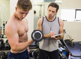 Instructor taking notes of muscular man lifting dumbbells