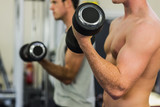 Two men lifting dumbbells