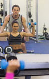 Reflection of instructor correcting woman lifting dumbbells