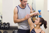 Instructor correcting smiling woman lifting dumbbells