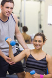 Instructor correcting happy woman lifting dumbbells