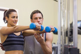 Instructor assisting happy woman lifting dumbbells