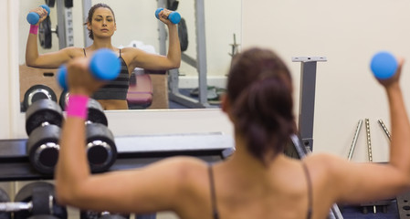 Toned woman lifting dumbbells looking into mirror