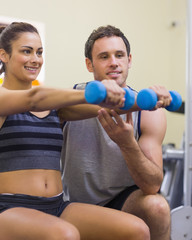 Instructor assisting smiling woman lifting dumbbells