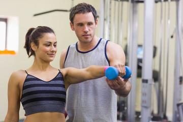 Instructor assisting content woman lifting dumbbells