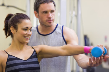 Instructor assisting cheerful woman lifting dumbbells