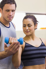 Instructor assisting content brunette lifting dumbbells