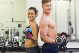 Topless man and smiling woman holding dumbbells