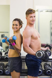 Smiling man and woman holding dumbbells