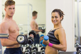 Sporty man and woman holding dumbbells
