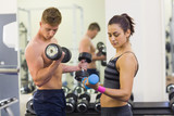 Determined man and woman holding dumbbells