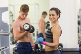 Determined man and smiling woman holding dumbbells