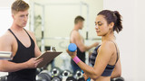 Muscular instructor taking notes of woman with dumbbells