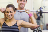 Instructor helping smiling woman lifting barbell