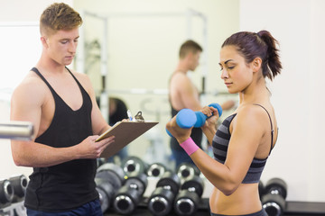 Instructor taking notes of woman lifting dumbbells