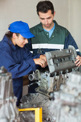 Trainee repairing engine with instructor