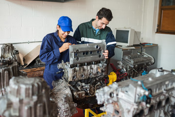 Smiling trainee and instructor checking engine