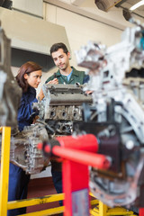 Concentrating trainee and instructor repairing an engine