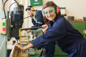 Smiling trainee with safety glasses drilling wood