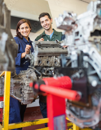 Happy trainee and instructor repairing an engine