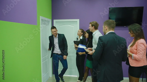 Attractive team of young professionals, in turn, come to office
