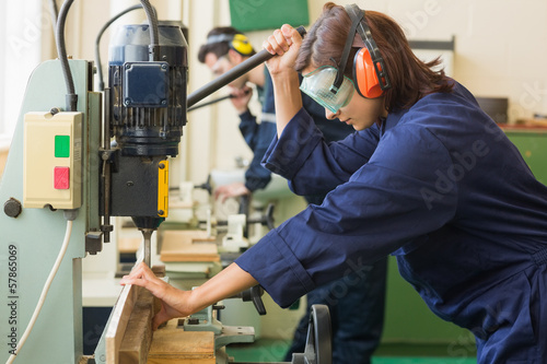 Trainee with safety glasses drilling wood