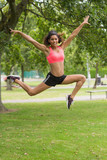 Full length of a toned woman jumping in park