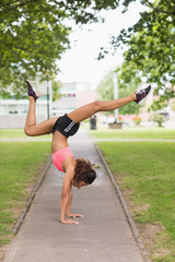 Toned woman performing a handstand in park