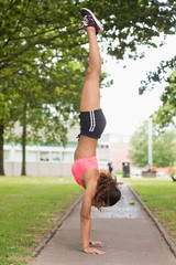 Toned young woman performing a handstand in park
