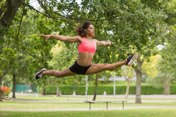 Toned woman performing the splits jump in park