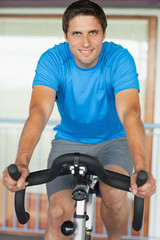 Man working out at spinning class in gym
