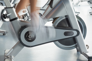 Low section of man working out at spinning class