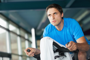 Determined young man working out at spinning class