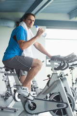 Tired man with water bottle working out at spinning class