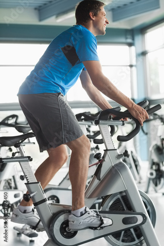 Smiling man working out at spinning class in gym