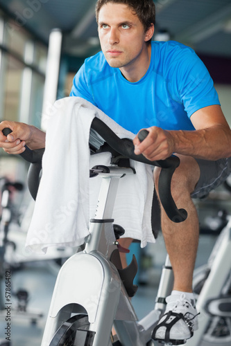 Determined man working out at spinning class