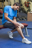 Healthy man with an injured leg sitting in the gym