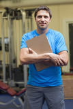 Smiling trainer with clipboard in the gym