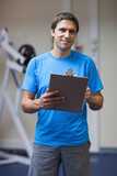 Portrait of a smiling trainer with clipboard in gym
