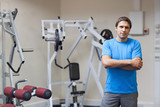 Smiling trainer with arms crossed against lat machine in gym