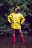 Smiling woman in yellow raincoat and red gumboots against trees