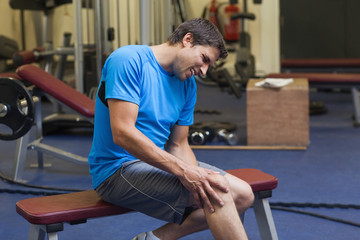 Healthy man with an injured leg sitting in gym
