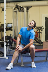 Healthy young man with an injured knee sitting in the gym