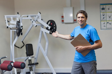 Trainer with clipboard pointing toward lat machine in gym