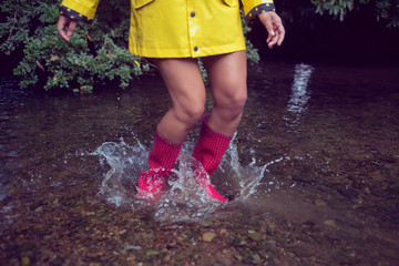 Woman in yellow raincoat and red gumboots jumping in water