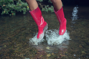 Woman in red gumboots jumping in water